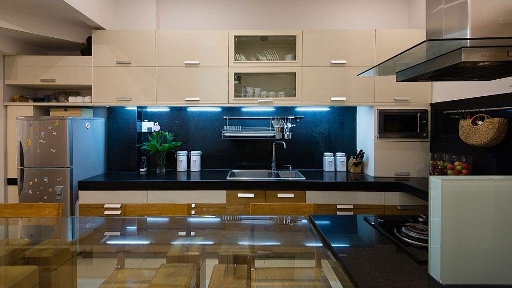 White cabinets and a dark backsplash fashion a cool, modern kitchen