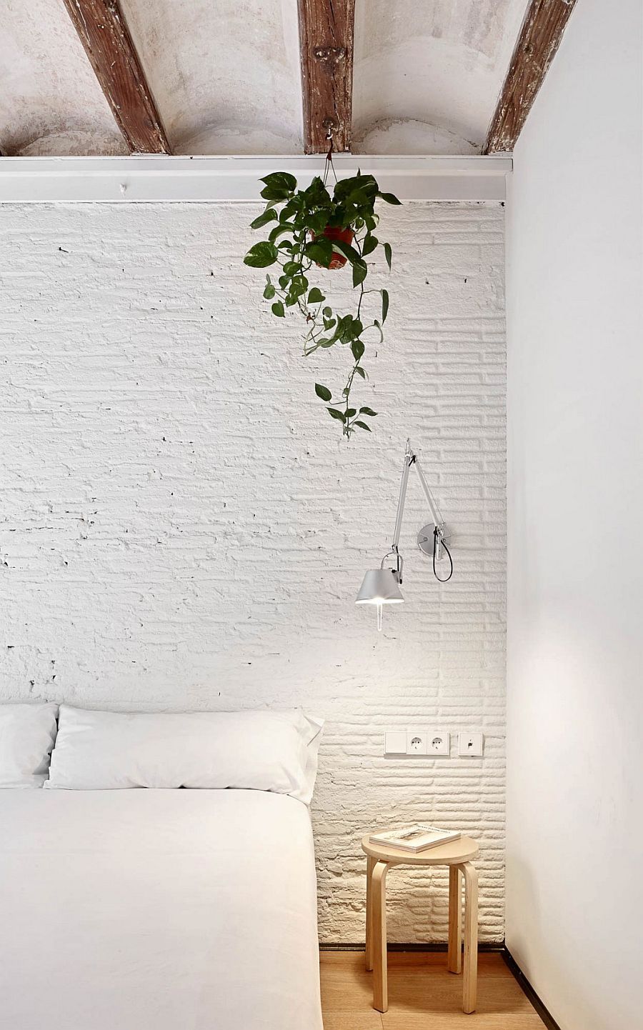 White painted ceiling, brick walls and exposed wooden beams of the Barcelona home