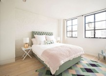 Whitewashed exposed brick wall and colorful rug with geometric pattern in the bedroom