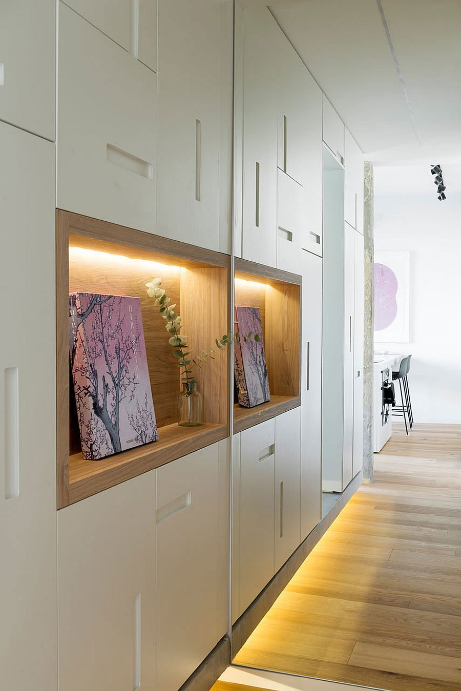Wooden niches surrounded by bespoke cabinets at the entrance of the apartment