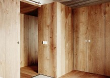 Wooden walls create smart partitions and private zones inside the tiny tourist apartment