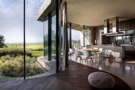 Curved seat along with the kitchen and dining area inside the sustainable dutch home