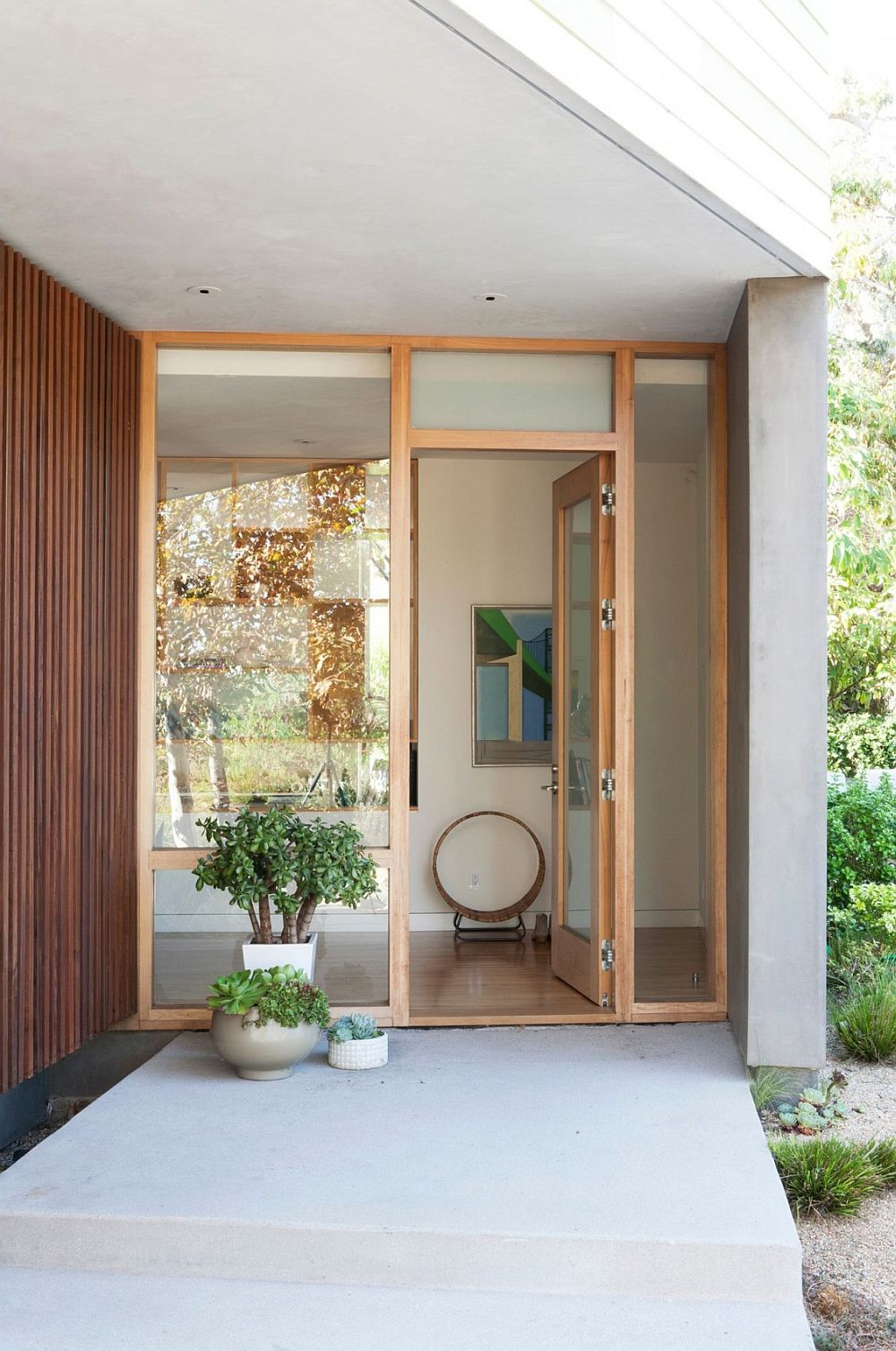 Entryway to the relaxing modern home in Santa Monica, California with wooden slats and potted plants