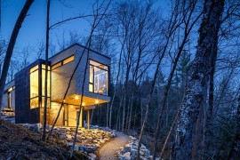 Light adds inviting warmth and sparkle to the cottage in woods