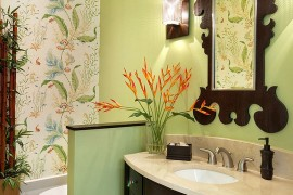Mirror frame seems to complement the pattern of Thibaut wallpaper in the powder room