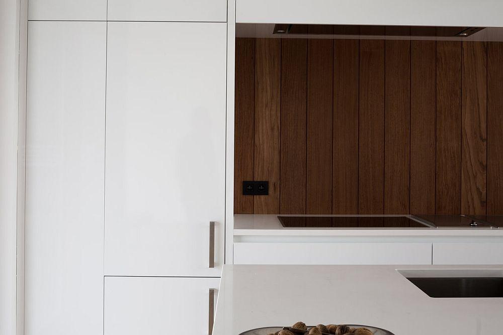 Modern kitchen in white with wooden backsplash