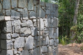 Outdoor shower area with stone wall