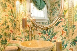 Tropical powder room with turquoise vanity, glittering lighting and bold wallpaper