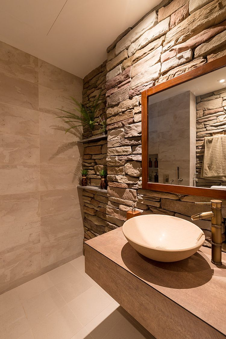 Tropical style powder room with a stacked stone wall [Design: Interi Living]