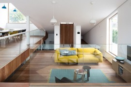 View of the living area with a bright yellow couch and ample natural light