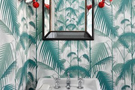 Wall sconce add a pop of red to the delightful powder room