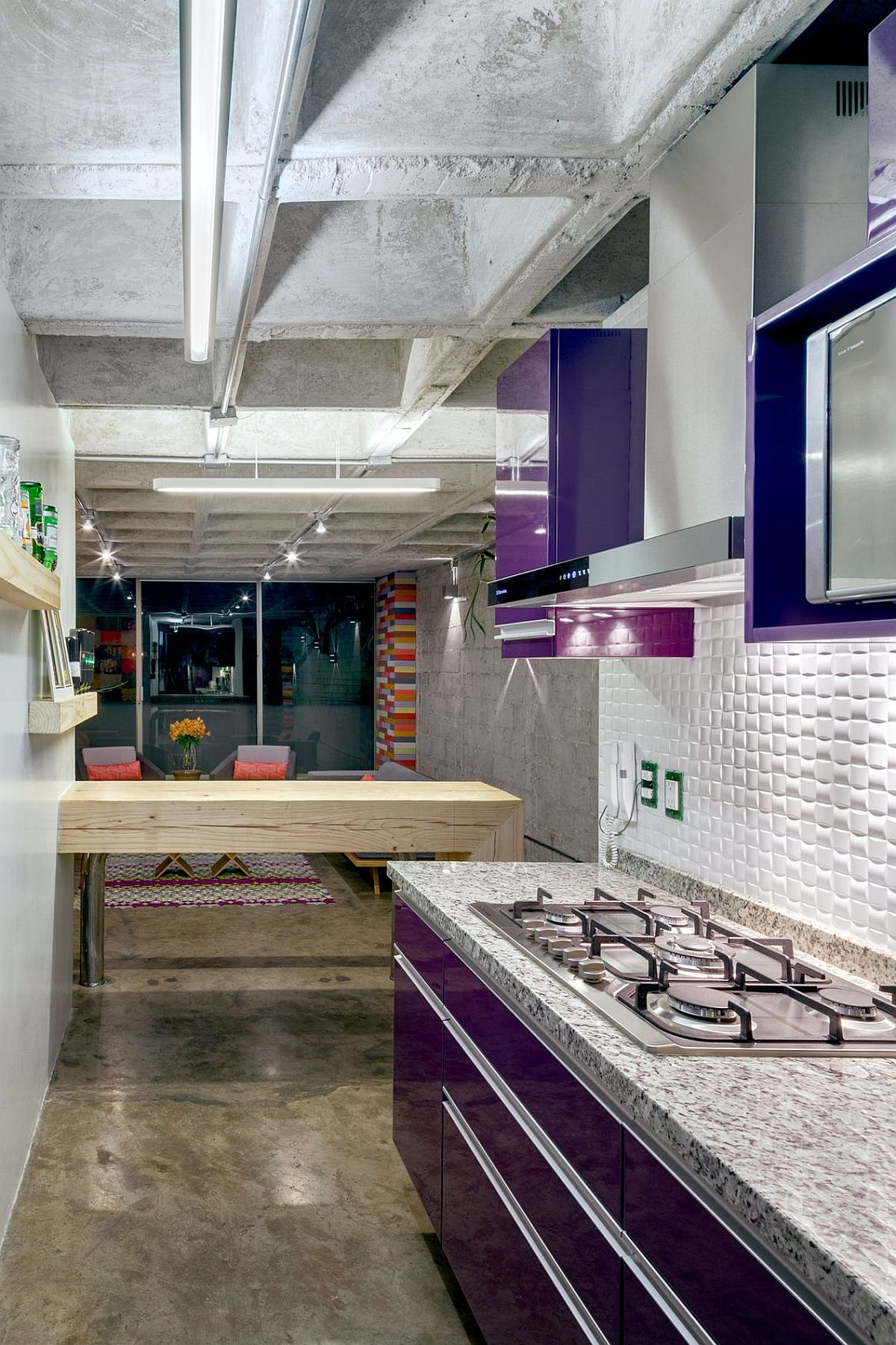 Aubergine-purple polyester cabinets and recycled timber breakfast bench inside the small kitchen