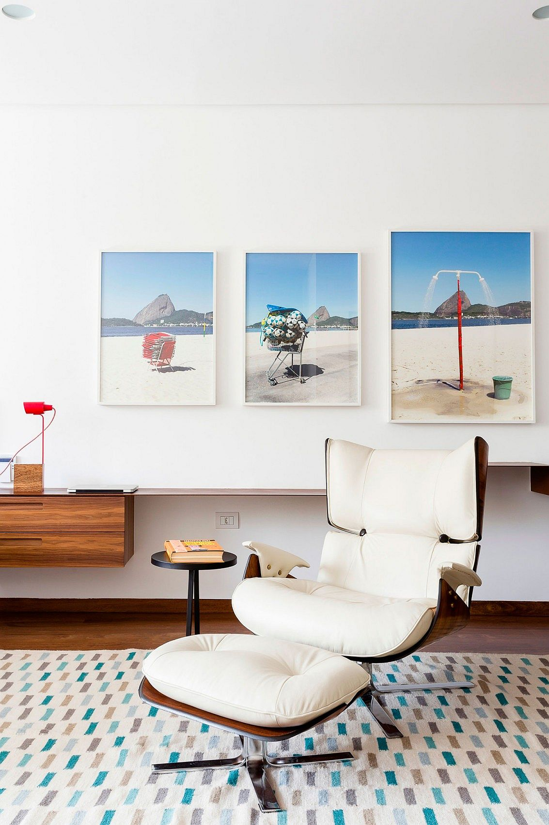 Beach-themed photographs set the mood in the bedroom of the Brazilian home