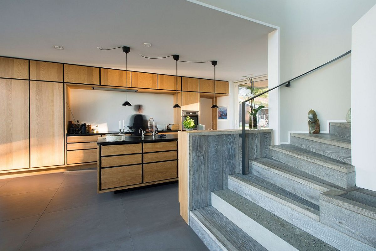 Beautiful contemporary kitchen with wooden cabinets, island and dark lines that anchor it visually