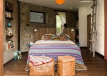 Bedroom with stone accent wall and colorful bedding