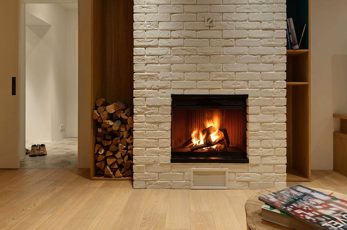Brick fireplace with stacked wood next to it