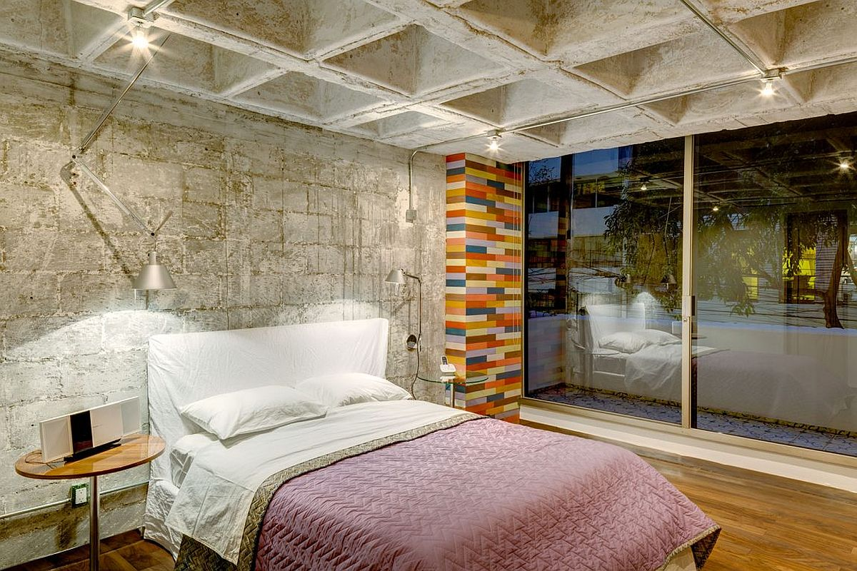 Contemporary bedroom with custom wooden flooring and concrete walls