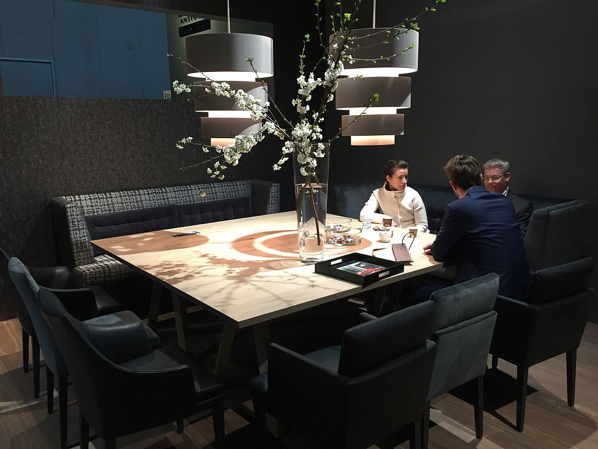 Dark and dramatic setting of the JAB Anstoetz stand at Milan 2016 showcases a smart dining room setup