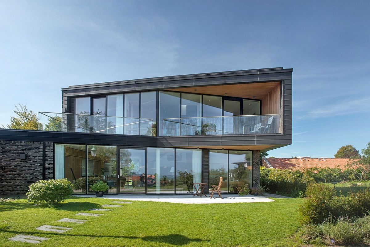 Dark patinated zinc and glass shape the facade of the spacious home in Denmark