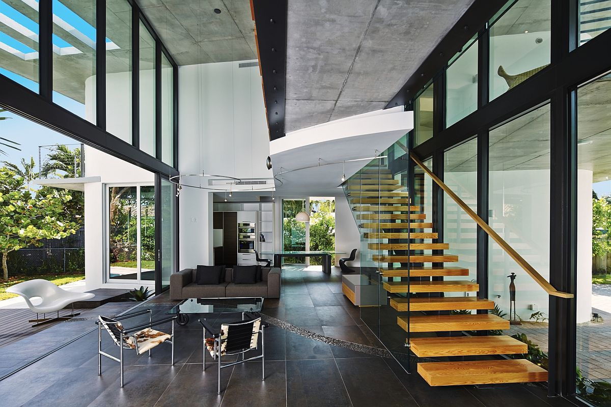 Exquisite living area with glass walls and floating staircase