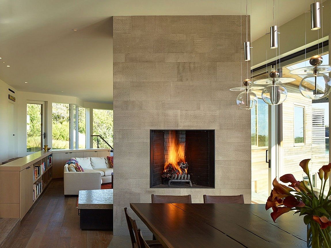 Fireplace delineates the dining space from the living room