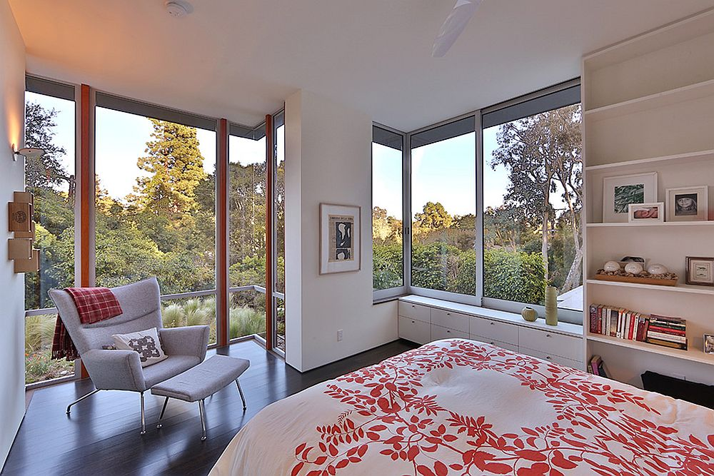 Floor-to-ceiling glass windows open up the bedroom towards the veiw outside