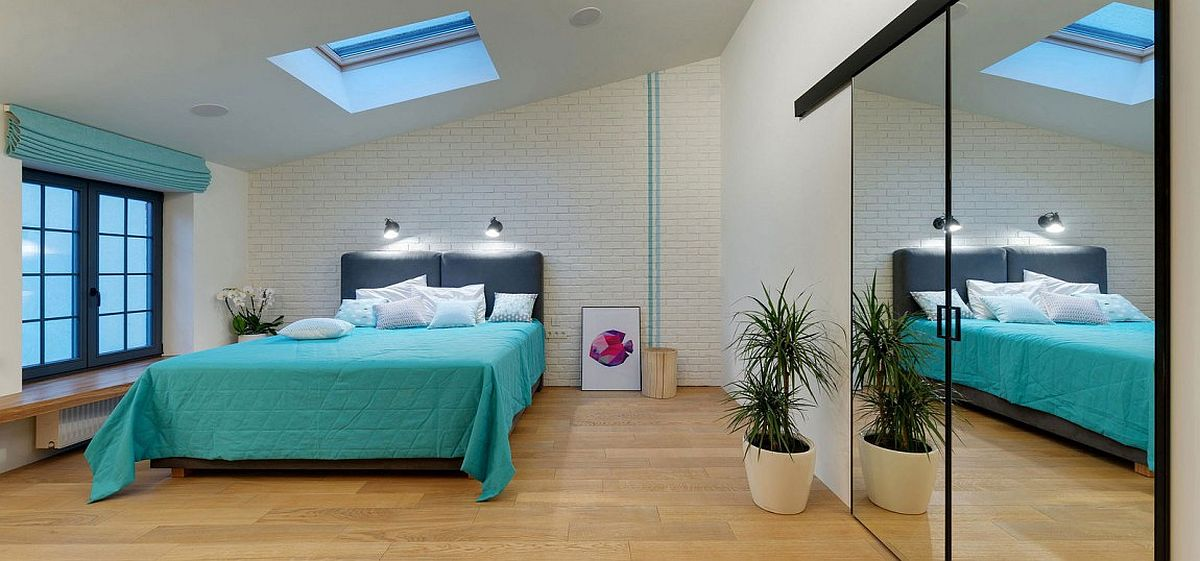 Gorgeous bedroom in white and blue with a brick accent wall