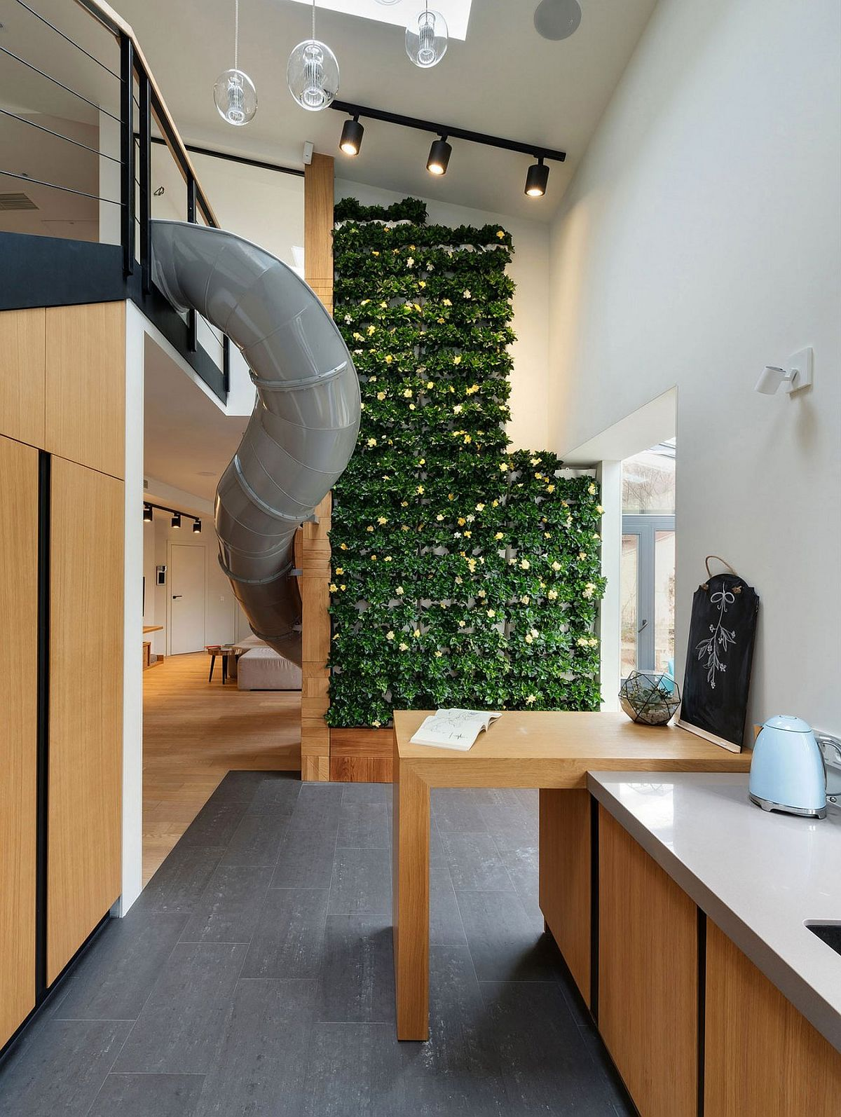 Green wall and slide shape a stunning and fun apartment in Ukraine