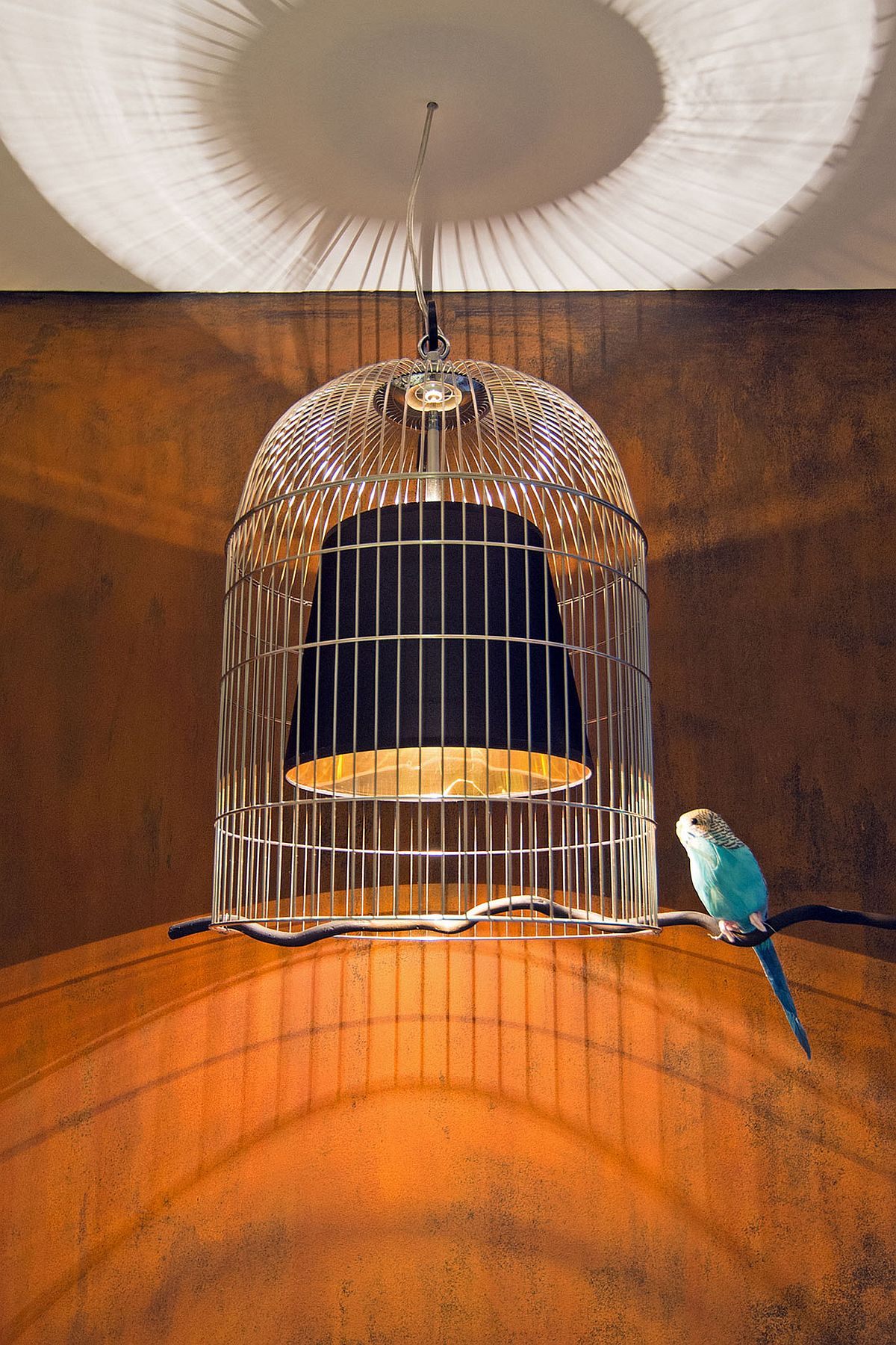 Ingenious and playful pendant light design with a birdcage around it