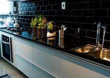 Kitchen with black countertop and black tiled backsplash