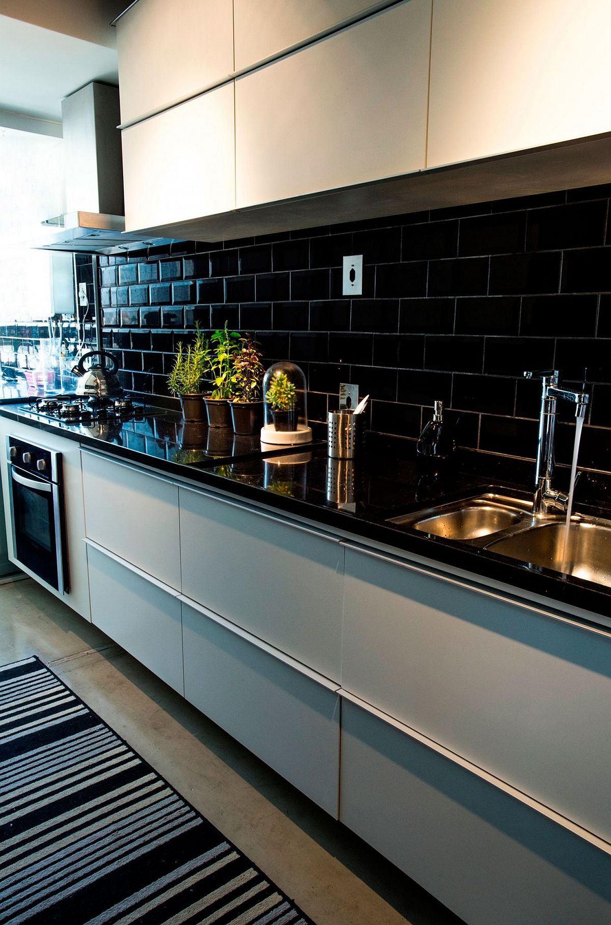 Kitchen with black countertop and black tiled backsplash