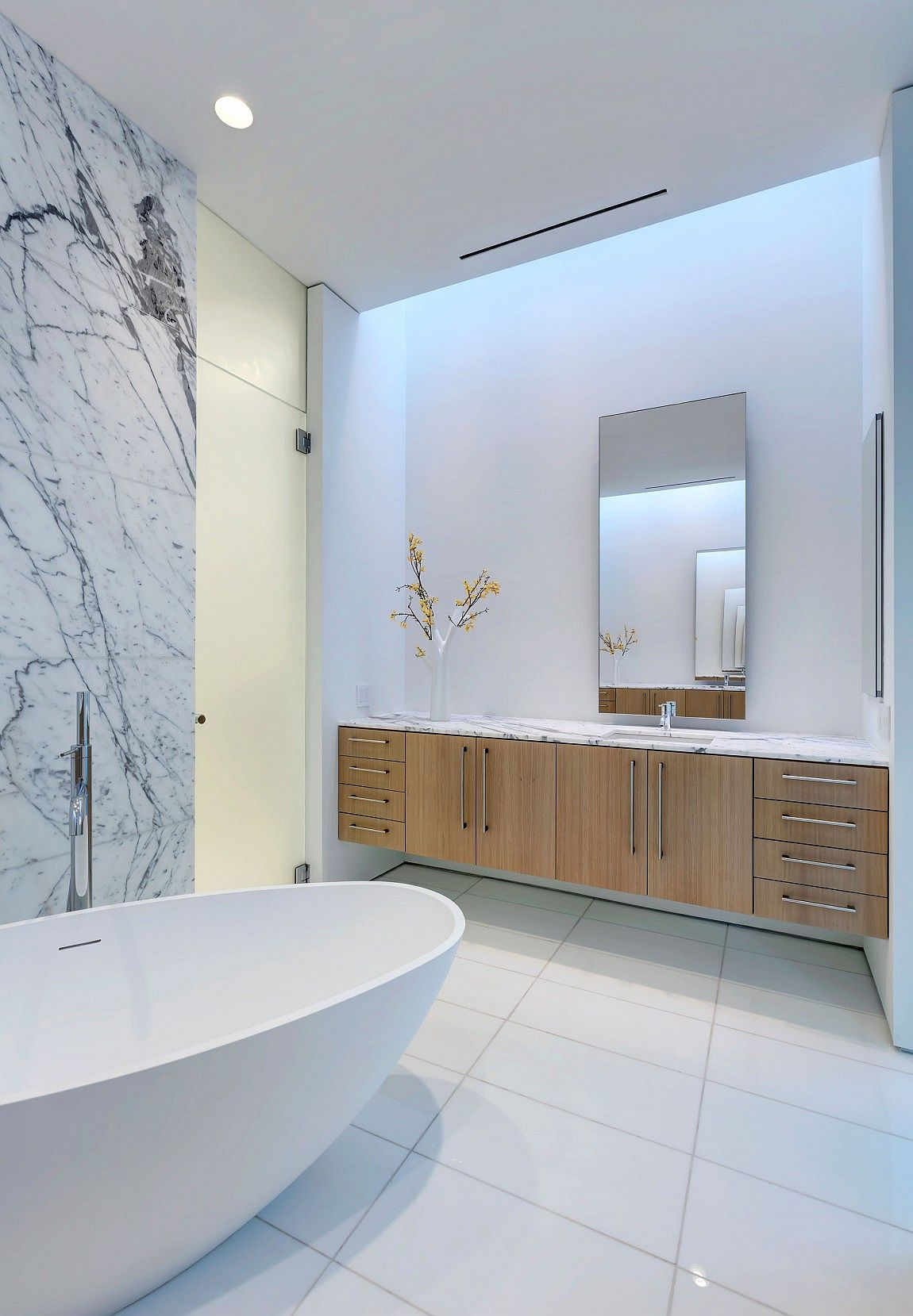 Marble countertops and background add an air of luxury to the contemporary bathrooom