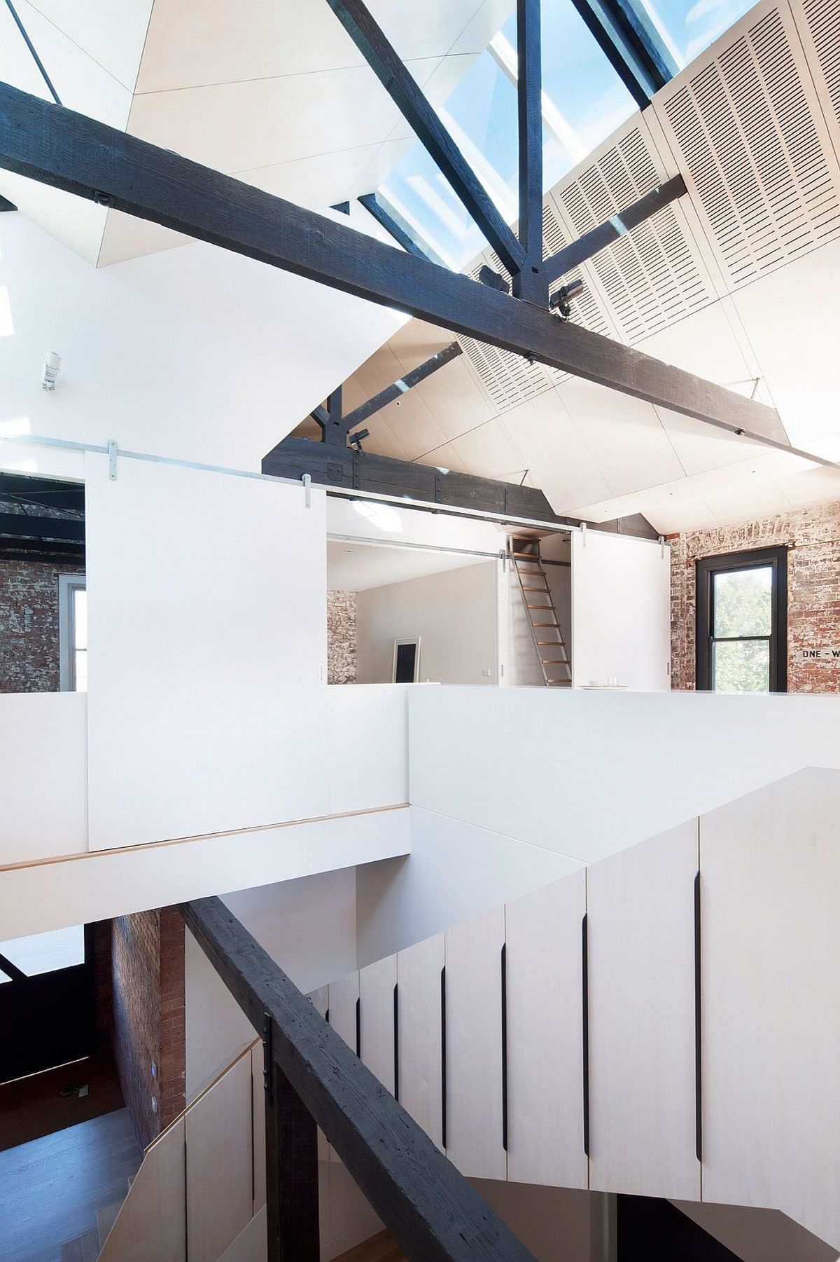 Original roof trusses and modern ceiling meet inside the converted warehouse residence