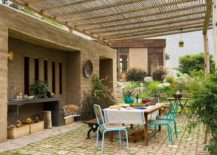 Outdoor dining space surrounded by a beautiful wall of greenery and fetauring an outdoor worktop