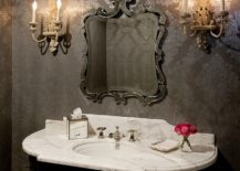 Sconce lighting and wallpaper bring Victorian style to this powder room