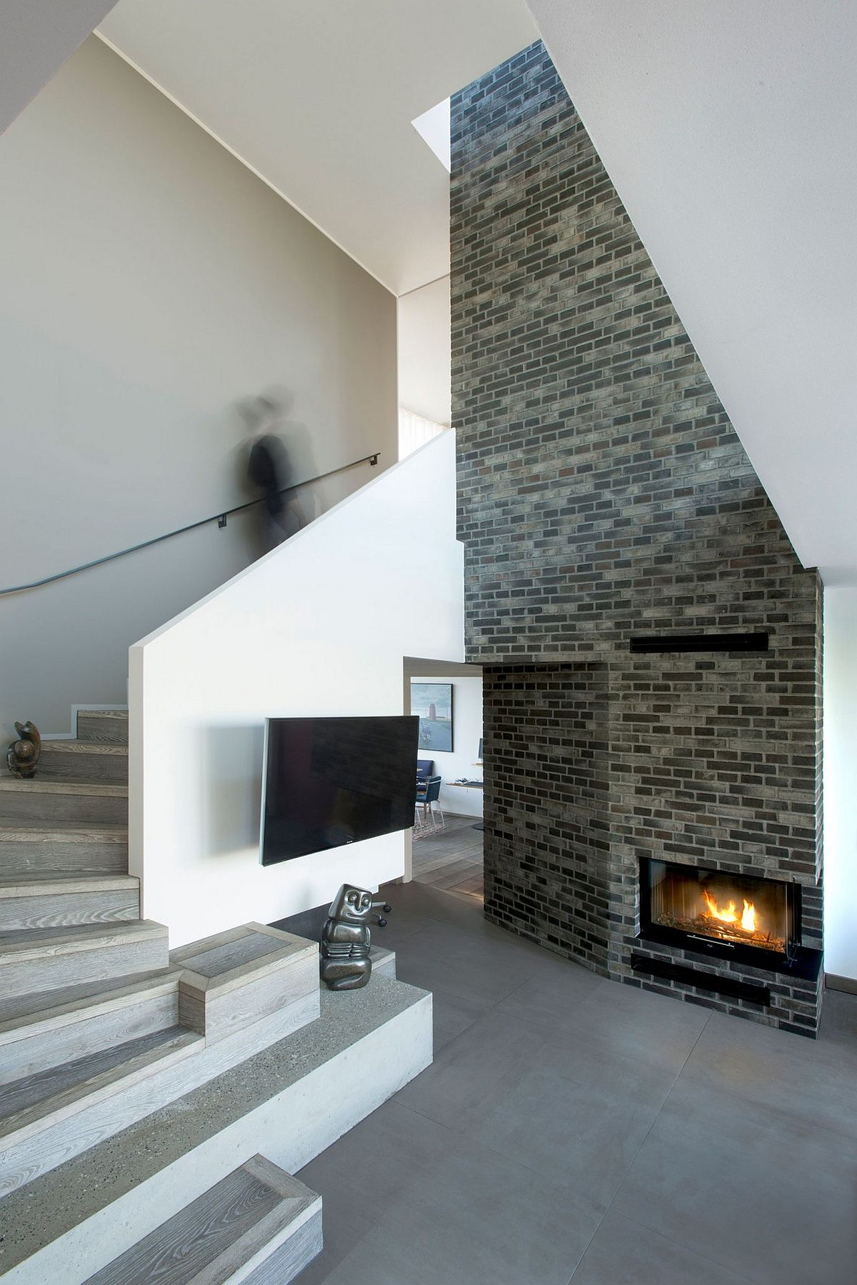 Sculptural staircase and brick fireplace inside the contemporary residence in Denmark