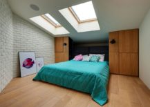Skylights bring in light into the bedroom on the top level with brick walls