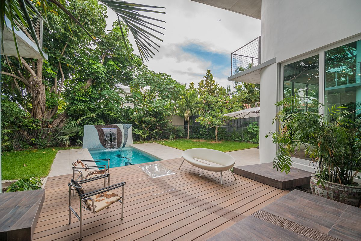 Spacious backyard, wooden deck and pool of the contemporary home