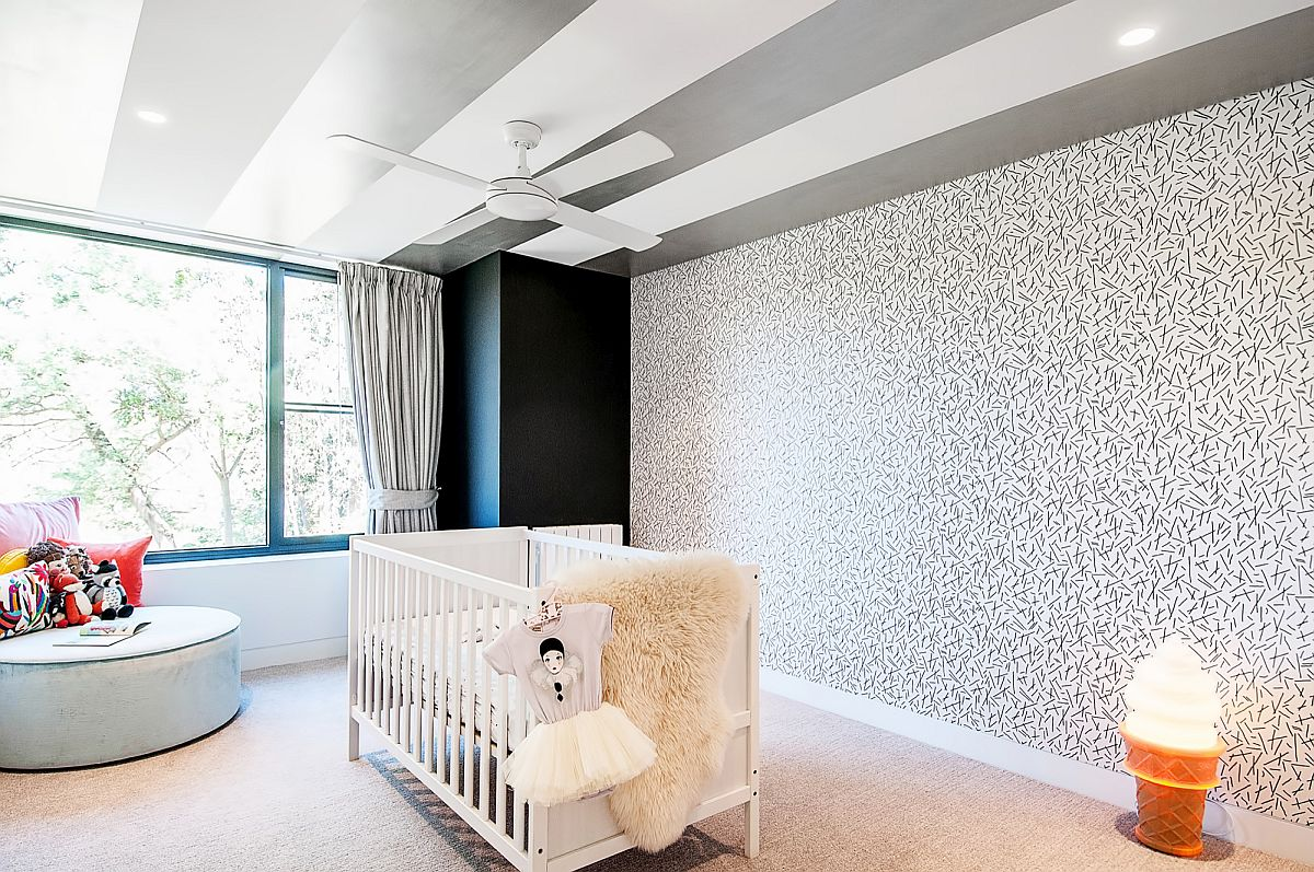 Wallpapered accent wall in the nursery uses less color and more pattern