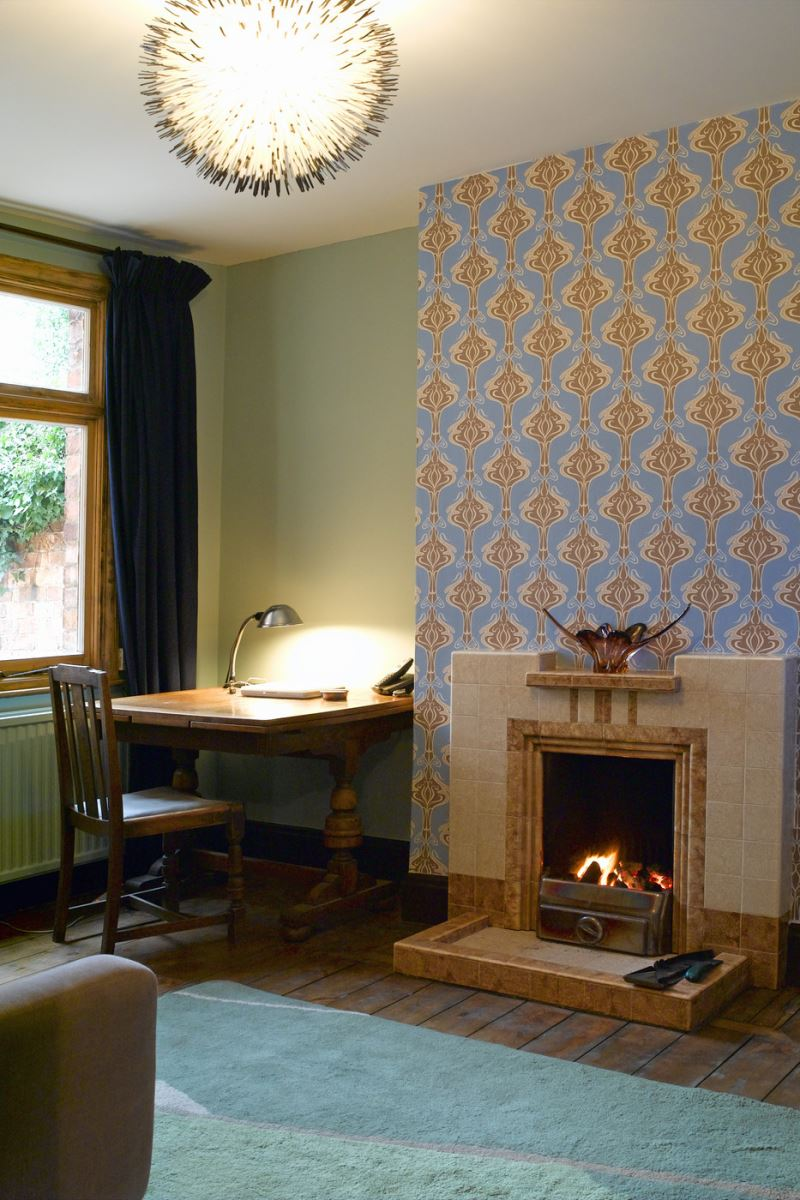 Wallpapered accent wall with a fireplace