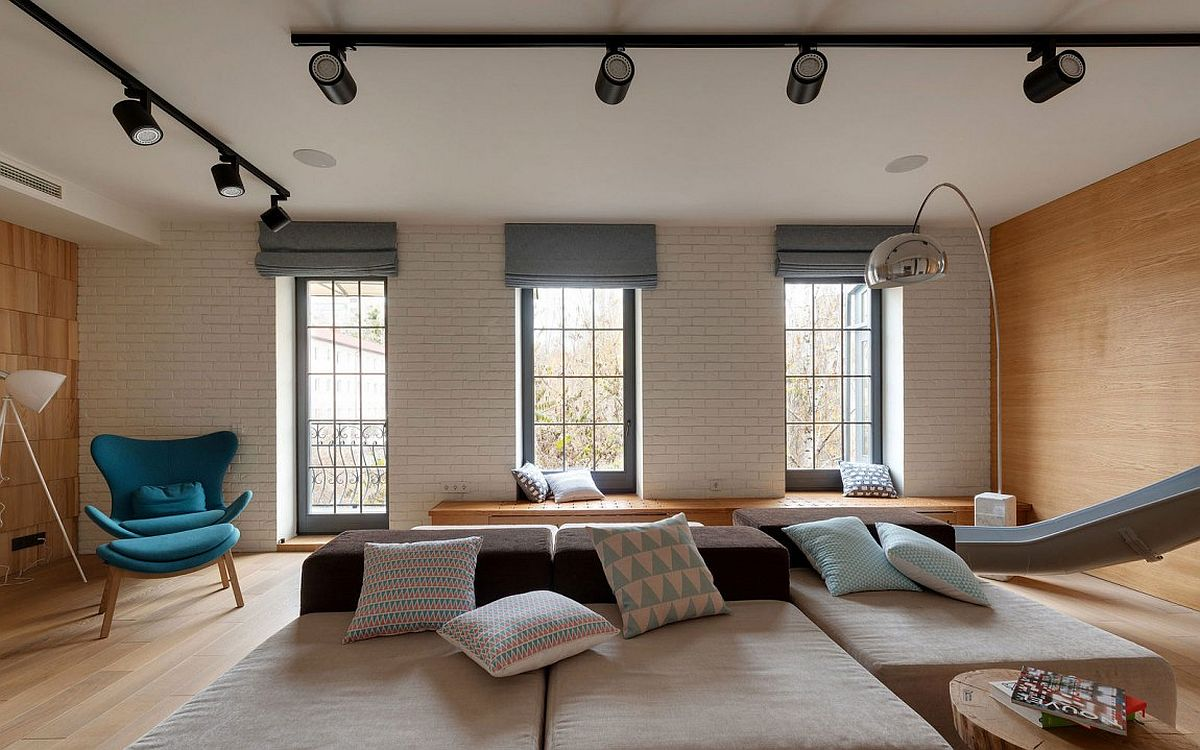 White brick wall adds contrats to the living room visual along with the rich wooden surfaces