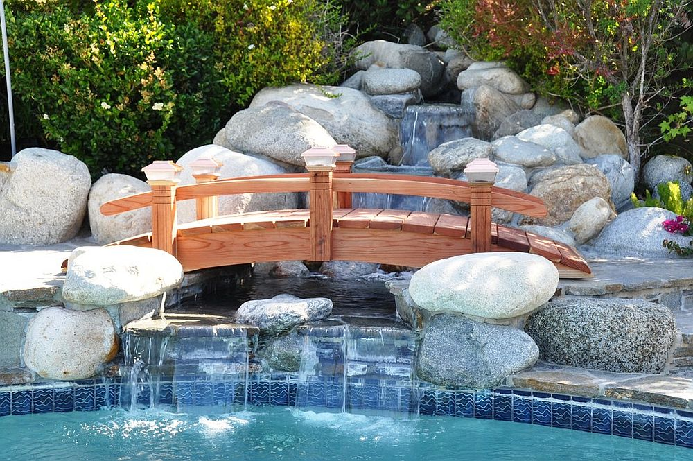Arched wooden bridge over the water garden is a great way to complete your poolscape [Design: Redwood Garden Bridges]