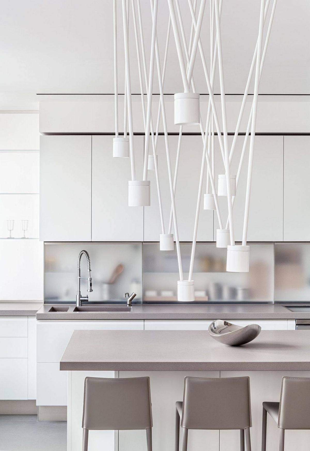 Bespoke lighting fixture above the dining space adds intrigue