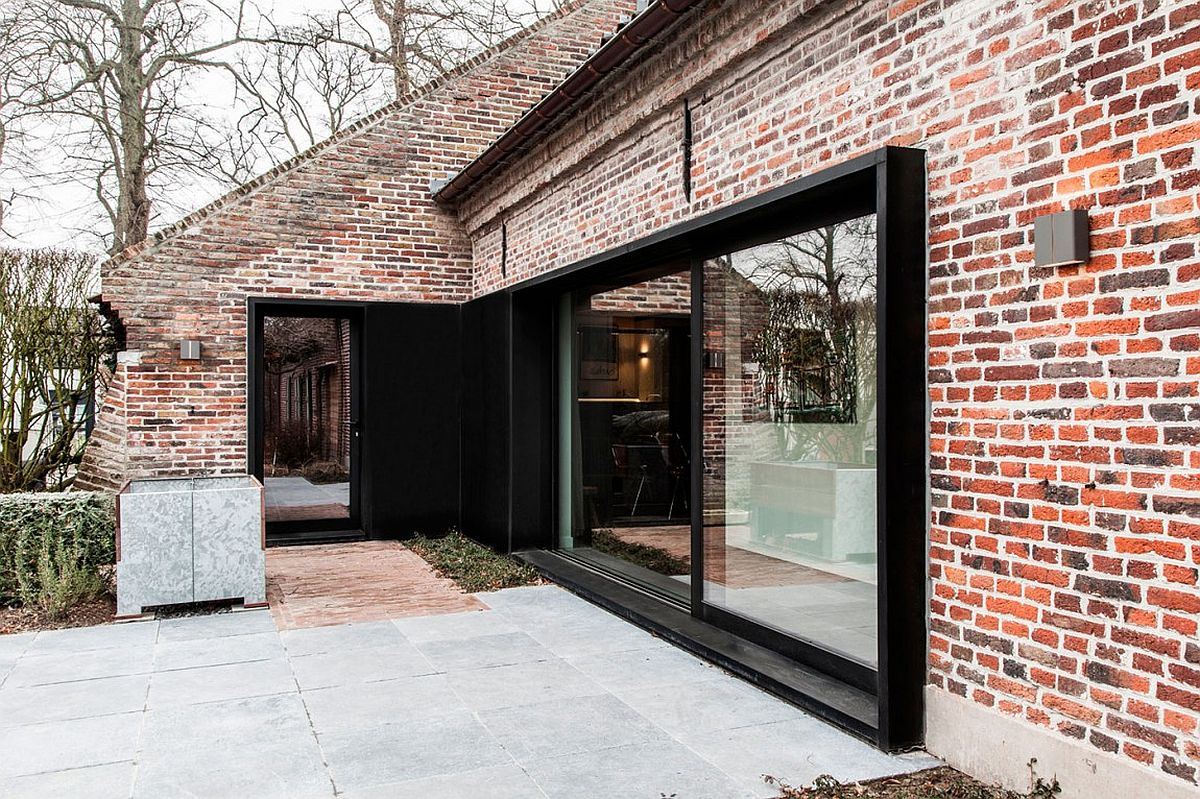 Brick exterior of the old farm house given a new, dark window with sliding glass doors