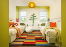 Bright and cheerful kids' room with twin beds seems super fun thanks to the multi-colored rug