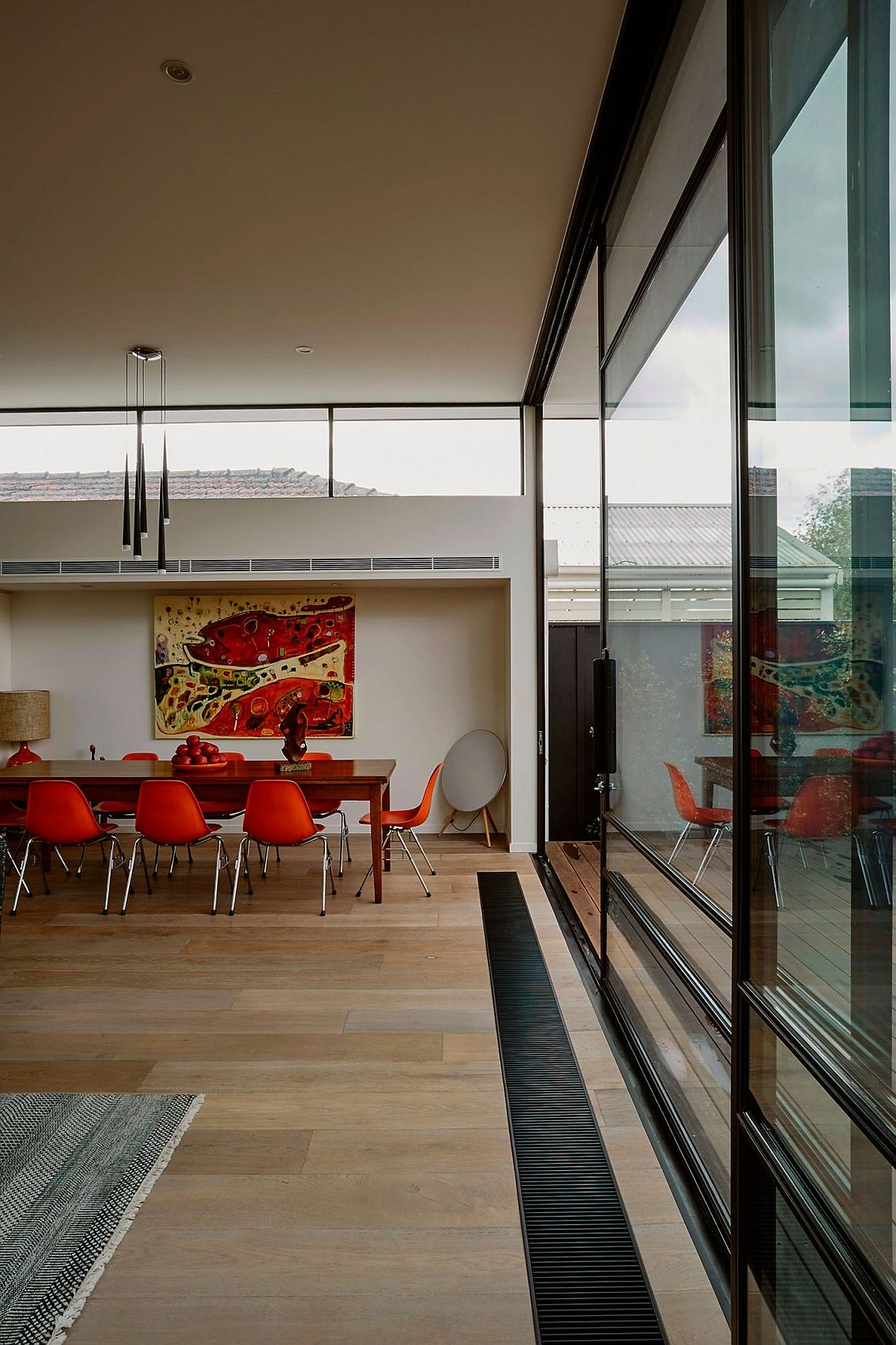 Bright orange chairs and art work add color to the neutral dining space