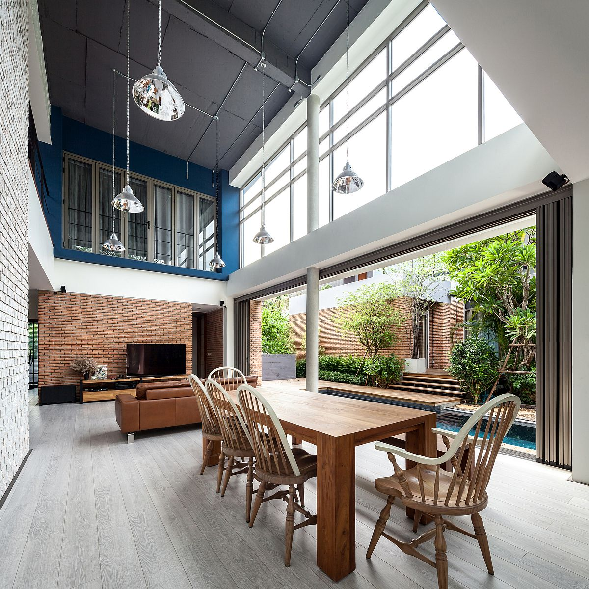 Charming open plan living in white and blue with brick walls all around