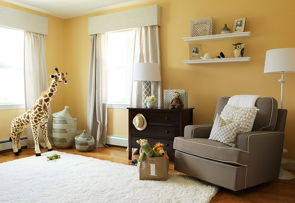 Comfy gray chair provides contrast to the lovely yellow backdrop in the nursery [Design: Victoria Elizabeth Design]