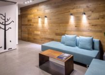 Contemporary sofas in pastel blue and wall covered in wooden panels create a smart lounge