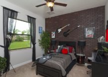Cool teen bedroom with accent brick wall and guitar on the walls